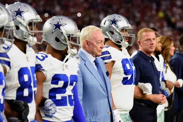 Dallas Cowboys' owner Jerry Jones (blue jacket) stands with his players before the national anthem before the Cowboys play the Arizona Cardinals
